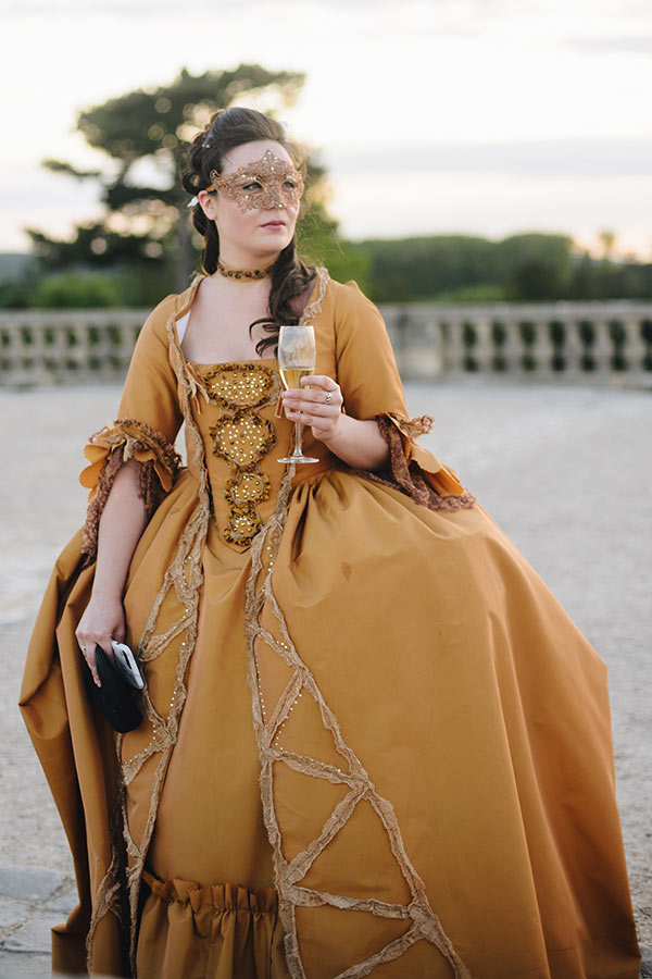 At Versailles, young and beautiful lady wearing with elegance a masquerade ball dress